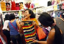 Domestic helper Lisa Padua (2nd R) jokes as she shops for clothes with her friends on a day off, at Lucky Plaza in Singapore October 20, 2013. REUTERS/Edgar Su