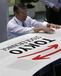 Сотрудник Токийской фондовой биржи 20 мая 2013 года. Азиатские фондовые рынки завершили торги вторника разнонаправлено в ожидании отложенной американской статистики. REUTERS/Toru Hanai