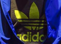 Логотип Adidas на футболке во время ежегодной пресс-конференции компании в Херцогенаурахе 7 марта 2013 года. Второй в мире производитель спортивных товаров Adidas меняет схему управления своими подразделениями в Северной Америке и Западной Европе с целью ускорить рост в этих регионах, сообщила компания во вторник. REUTERS/Michael Dalder