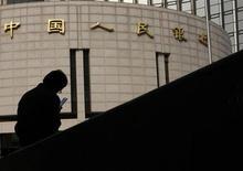 Homem sentado em frente à sede do Banco do Povo da China, banco central do país, em Pequim, 17 de outubro de 2013. O BC chinês limitou as operações de liquidez pelo segundo dia consecutivo nesta terça-feira à medida que reguladores dão sinais de preocupação sobre a possibilidade de a alta liquidez alimentar uma nova rodada de expansão arriscada de crédito. 17/10/2013 REUTERS/Kim Kyung-Hoon