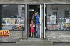 A resident and his child walk out of a convenience store, in a part of the town that has been reopened today, in Lac Megantic, July 9, 2013. REUTERS/Mathieu Belanger