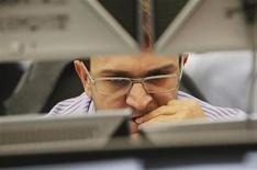 Трейдер в торговом зале Тройки Диалог в Москве 26 сентября 2011 года. Российский фондовый рынок во вторник колеблется с незначительными изменениями котировок, а повышенный спрос участники торгов отмечают только на бумаги группы ТКС, которые начали сегодня обращаться на Лондонской бирже. REUTERS/Denis Sinyakov