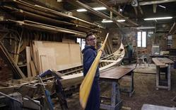 """A gondolier holds an oar of his gondola at the San Trovaso boatyard known as a """"squero"""", in Venice October 14, 2013. REUTERS/Stefano Rellandini"""
