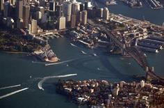 The Sydney Harbour Bridge casts a shadow next to the Sydney Opera House and central business district (CBD) as boats make their way along the harbour in this picture taken July 21, 2013. REUTERS/David Gray