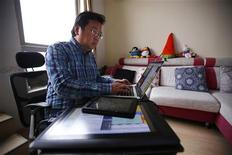 Chinese cartoonist Wang Liming uses his computer inside his apartment before an interview with Reuters in Beijing, Ocotober 22, 2013. REUTERS/Petar Kujundzic