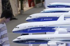 Посетитель выставки Aviation Expo смотрит на модели самолетов Boeing в Пекине 25 сентября 2013 года. Прибыль Boeing Co на акцию выросла на 12 процентов в третьем квартале, позволив компании повысить годовой прогноз прибыли и отправив её акции в 3-процентный рост на предбиржевых торгах REUTERS/Kim Kyung-Hoon