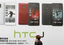 Una mujer charla por teléfono móvil frente a un anuncio de HTC en Taipéi, ene 7 2013. - El fabricante taiwanés de teléfonos inteligentes HTC Corp suspendió al menos una de sus cuatro principales líneas de manufactura, lo que representa al menos una quinta parte de su capacidad total, y está externalizando producción en momentos en que una caída en las ventas pone presión sobre su flujo de efectivo, de acuerdo a fuentes con conocimiento directo de la situación. REUTERS/Pichi Chuang
