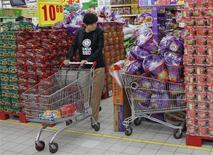 Una mujer observa los precios de fideos en un supermercado en Pekín, oct 9 2013. Los temores a la inflación crecieron el miércoles en Asia al intensificarse las presiones de los precios en Australia, al tiempo que las tasas de interés de corto plazo de China se disparaban al alza por preocupaciones de que el banco central pueda ajustar pronto la liquidez. REUTERS/Kim Kyung-Hoon