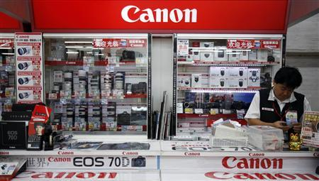 A shop staff works at Canon's camera booth at an electronic shop in Tokyo October 24, 2013. REUTERS/Yuya Shino