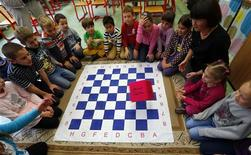 "Children use a ""chess dice"" during a lesson at the Dezso Lemhenyi school, which uses the new ""Chess Palace"" teaching program of the world's best female chess player Judit Polgar, in Budapest October 15, 2013. REUTERS/Laszlo Balogh"