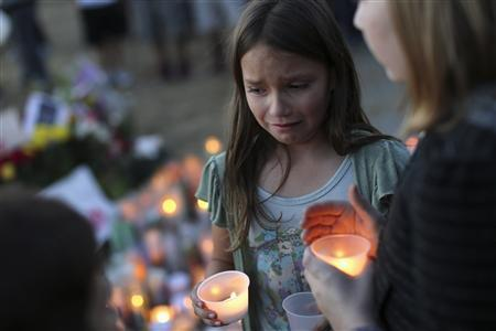 Denae Kirtley lights a candle at the site of the death of Andy Lopez Cruz in Santa Rosa, California October 24, 2013. REUTERS/Robert Galbraith