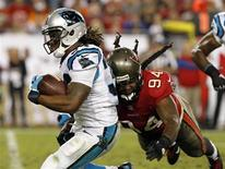 Oct 24, 2013; Tampa, FL, USA; Carolina Panthers running back DeAngelo Williams (34) runs with the ball as Tampa Bay Buccaneers defensive end Adrian Clayborn (94) defends during the second half at Raymond James Stadium. Kim Klement-USA TODAY Sports
