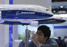 Мужчина фотографирует модели самолетов Boeing на выставке Aviation Expo в Пекине 25 сентября 2013 года. Около 200 лайнеров 737 Max хотят купить у Boeing Co различные китайские лизинговые и авиакомпании, сообщили два источника, близкие к договоренностям между покупателями и американским аэрокосмическим гигантом. REUTERS/Kim Kyung-Hoon