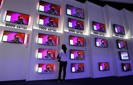 A woman looks at flat screen TV sets in the Philips pavilion before the opening of the IFA consumer electronics fair in Berlin, August 31, 2011. REUTERS/Thomas Peter