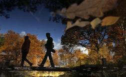 Отражение людей в воде в московском парке 12 октября 2013 года. Выходные в Москве будут теплыми, но облачными, ожидают синоптики. REUTERS/Maxim Shemetov
