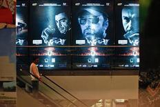 "A man rides an escalator past posters of the movie ""Waar"" at the Atrium cinemas in Karachi October 23, 2013. REUTERS/Akhtar Soomro"