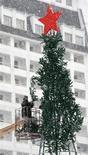 Рабочий устанавливает елку в центре Ставрополя 20 декабря 2007 года. Активность в российской экономике едва теплилась в третьем квартале, и только надежды на предновогоднее оживление потребительских расходов и инвестиций позволяют Минэкономики не пересматривать и без того пессимистичный прогноз роста ВВП на 1,8 процента по итогам 2013 года. REUTERS/Eduard Korniyenko
