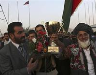 Afghan cricket team captain Mohammad Nabi Esa Khil (C) holds the ACC Cup after the team's arrival in Kabul, in this October 12, 2013 file photo, following Afghanistan's qualification for the 2015 Cricket World Cup. REUTERS/Omar Sobhani/Files