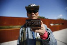 A tour guide poses for photographs with a stamp for tourists at the Imjingak pavilion near the demilitarized zone which separates the two Koreas, in Paju, north of Seoul October 16, 2013. REUTERS/Kim Hong-Ji