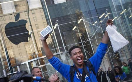 One of the first customers to purchase the Apple iPhone 5S celebrates after exiting the Apple Retail Store on Fifth Avenue in Manhattan, New York September 20, 2013. REUTERS/Adrees Latif
