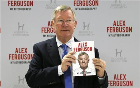 Former Manchester United manager Alex Ferguson poses with his new autobiography before a book signing at a supermarket in Manchester, northern England October 24, 2013. REUTERS/Phil Noble