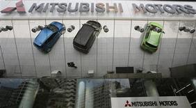 Mitsubishi Motors Corp's vehicles and a passer-by are reflected on an external wall at the company headquarters in Tokyo May 23, 2013. REUTERS/Toru Hanai