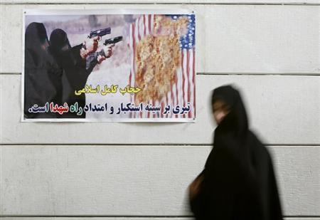 An Iranian woman walks past an anti-U.S. poster during a visit to a war museum in the city of Khorramshahr, 1350 km (844 miles) southwest of Tehran in Khoozestan province, March 14, 2007. REUTERS/Morteza Nikoubazl