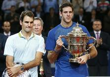 Juan Martin Del Potro (R) of Argentina poses with the winner's trophy after he won his final match against Switzerland's Roger Federer (L) at the Swiss Indoors ATP tennis tournament in Basel October 27, 2013. REUTERS/Arnd Wiegmann