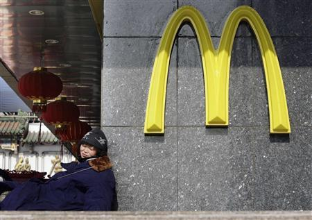 A woman rests outside a McDonald's outlet in Beijing in this February 5, 2009 file photo. REUTERS/Jason Lee/Files