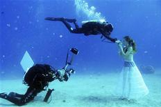 A model opens her mouth to breathe from a scuba tank as Israeli photographer Johannes Felten (L) takes pictures during an underwater photo shoot in the Red Sea in the resort city of Eilat October 22, 2013. REUTERS/Gabriel Rif