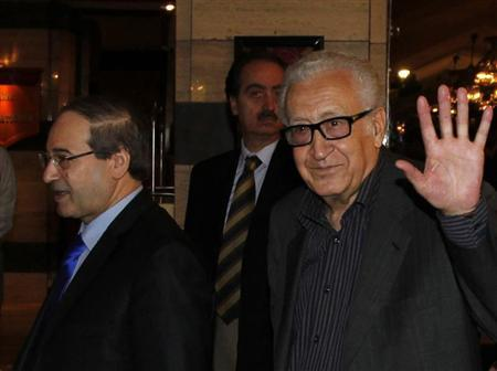 United Nations Peace Envoy for Syria Lakhdar Brahimi (R) waves to journalists during his arrival at a hotel in Damascus October 28, 2013. Seen at left is Syria's Deputy Foreign Minister Faisal al-Miqdad. REUTERS/Khaled al-Hariri