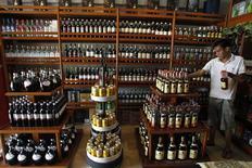 Un trabajador arregla botellas de vino en una tienda en Manila, jul 5 2013. La producción mundial de vino repuntó con fuerza este año y alcanzó niveles vistos por última vez en el 2006 debido a que una mayor producción en las viñas contrarrestó una fuerte caída en el área plantada, dijo el lunes la Organización Internacional de Vides y Vinos (OIV, por su sigla en inglés). REUTERS/Romeo Ranoco