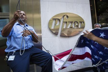 Workers raise a U.S. flag outside the Pfizer building in New York September 4, 2013. REUTERS/Lucas Jackson