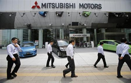 Men walk in front of Mitsubishi Motors Corp's headquarters in Tokyo May 23, 2013. REUTERS/Toru Hanai