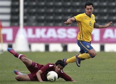 Sweden's Jiloan Hamad (R) fights for the ball with Qatar Olympic team's Mohammed AlJabri during their international friendly match in Doha January 23, 2012. REUTERS/Fadi Al-Assaad