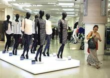 A shopper passes mannequins wearing the new autumn/ winter women's wear collection in Marks & Spencer's in central London on July 25, 2013. REUTERS/Olivia Harris