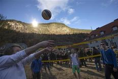 People play volleyball during the official opening of giant sun mirrors (top) erected on the mountainside, in the town of Rjukan October 30, 2013. REUTERS/Terje Bendiksby/NTB Scanpix