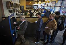 Customers line-up to use the world's first ever permanent bitcoin ATM unveiled at a coffee shop in Vancouver, British Columbia October 29, 2013. REUTERS/Andy Clark