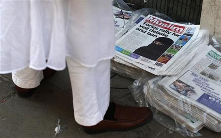 A man looks at newspapers outside the Brick Lane Jamme Masjid (mosque) before Friday prayers in east London September 20, 2013. REUTERS/Suzanne Plunkett