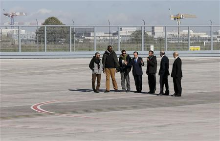 French President Francois Hollande (C), French Defence minister Jean-Yves Le Drian (R) and Foreign Affairs Minister Laurent Fabius (2ndR) walk with former French hostages Marc Feret (L), Thierry Dol (2ndL), Pierre Legrand (3rdL) and Daniel Larribe (3rdR) on the tarmac upon their arrival at Villacoublay military airport, near Paris, October 30, 2013. REUTERS/Philippe Wojazer