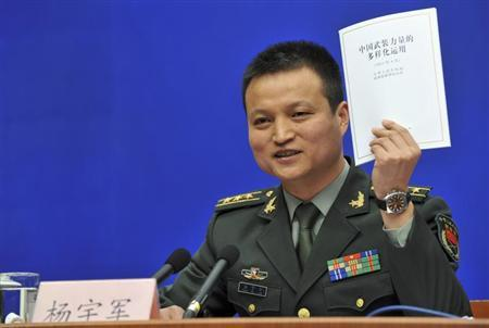 China's Ministry of Defence spokesman Colonel Yang Yujun speaks to journalists as he holds up the white paper on ''The Diversified Employment of China's Armed Forces'' during a news conference in Beijing, April 16, 2013. REUTERS/China Daily