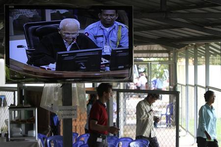 People enter the Extraordinary Chambers in the Courts of Cambodia (ECCC) as a television screen shows ''Brother Number Two'' Nuon Chea, in the outskirts of Phnom Penh October 31, 2013. REUTERS/Samrang Pring