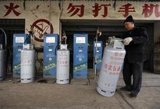Рабочий передвигает баллон со сжатым газом на газовой станции в китайском городе Тайюань в провинции Шаньси 25 ноября 2009 года. Газпром, потративший годы на споры о цене на газ с Пекином, рискует опоздать на жадный до энергоресурсов китайский рынок - опередить его могут более агрессивные российские конкуренты Новатэк и Роснефть. REUTERS/Stringer