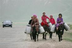 Женщины везут канистры с водой верхом на осликах в селении Гаргара, Таджикистан 4 мая 2008 года. Столица Таджикистана ввела в строй систему видеослежения на дорогах, купленную на китайский кредит в попытке снизить число нарушений, причину которых критики видят в безнаказанности обладателей роскошных авто в беднейшем постсоветском государстве. REUTERS/Nozim Kalandarov