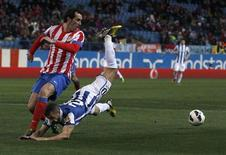 Atletico Madrid's Diego Godin (L) and Espanyol's Simao Sabrosa fight for the ball during their Spanish first division soccer match at Vicente Calderon stadium in Madrid February 24, 2013. REUTERS/Juan Medina