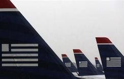 Avions de US Airways. Les autorités américaines de la concurrence souhaitent que cette compagnie et American Airlines acceptent des cessions avant de donner leur feu vert à une fusion qui donnerait naissance au numéro un mondial, a-t-on appris d'une source proche du dossier. /Photo prise le 12 juillet 2013/REUTERS/Larry Downing