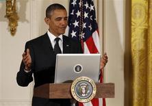 Presidente dos EUA, Barack Obama, reage após tuitar durante uma coletiva de imprensa na Casa Branca, em Washington. Em meio a muitas notícias desabonadoras sobre o lançamento do novo programa de saúde do governo federal, a Casa Branca quis desqualificar uma reportagem em especial. 6/07/2011. REUTERS/Larry Downing