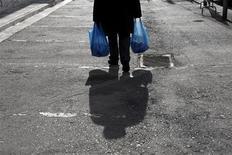 Un uomo per strada con due buste della spesa in plastica. REUTERS/Yorgos Karahalis