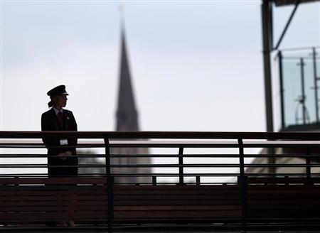 A G4S security guard watches over some of the courts at the Wimbledon Tennis Championships, in London June 26, 2013. REUTERS/Eddie Keogh