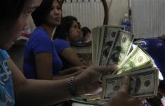 Una empleada revisa dólares en una casa de cambios en Manilas, sep 19 2013. El euro subía desde un mínimo en seis semanas contra el dólar el lunes, favorecido por datos que reflejaron que el sector manufacturero de la zona euro se aceleró el mes pasado. REUTERS/Romeo Ranoco